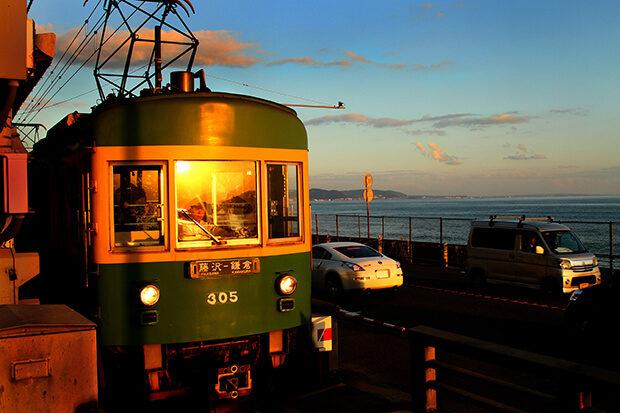 อ่าวซากามิที่ส่องแสงในดวงอาทิตย์ตกยามเย็นกับรถไฟฟ้าเอโนชิมะ