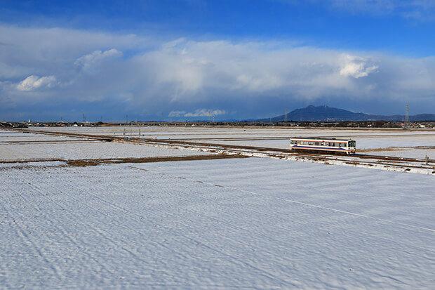 รถไฟฟ้าขบวน KIHA 2204 ที่แล่นในทุ่งนากลางทิวทัศน์หิมะ