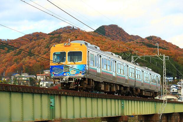 รถไฟขบวน แบบ700 ข้ามสะพานเหล็กโดยมีใบไม้เปลี่ยนสีเป็นฉากหลัง